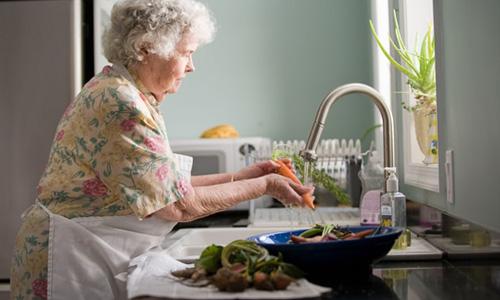 野菜を洗う主婦の画像