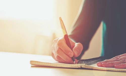 ノートに書いている人の画像