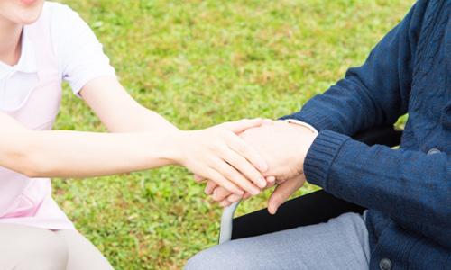 手をつなぐシニアと介護者